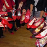 Hands offering different red shoes