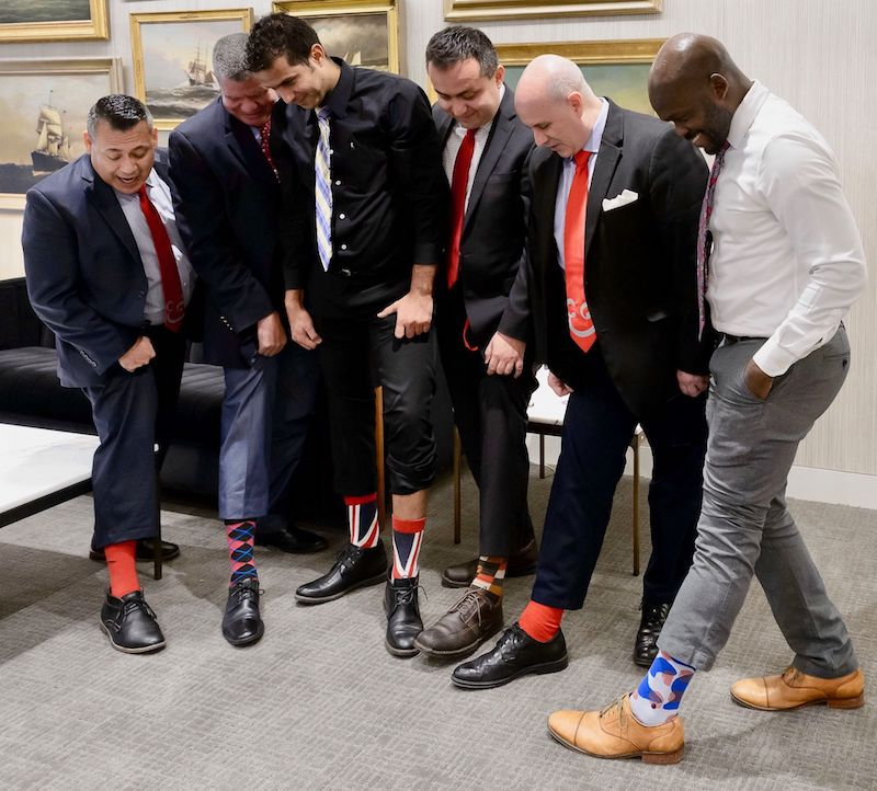 Male champions support women's career growth with red socks and ties on #RedTieTuesday