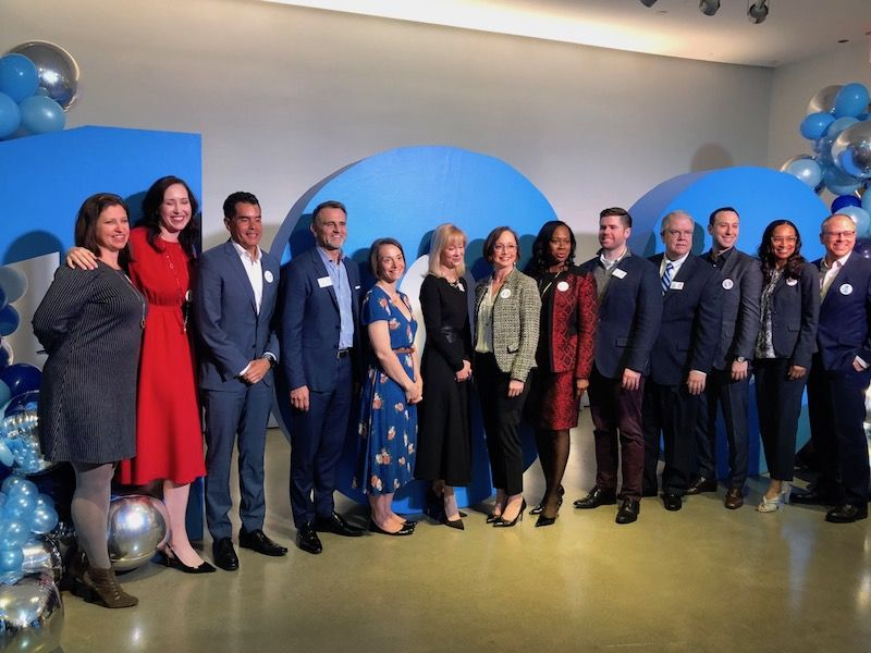 Katie Fallon in red, is a perfect example of how to leverage your personal traits in your job. Here with Hilton's top executives at a 100th birthday celebration media event.